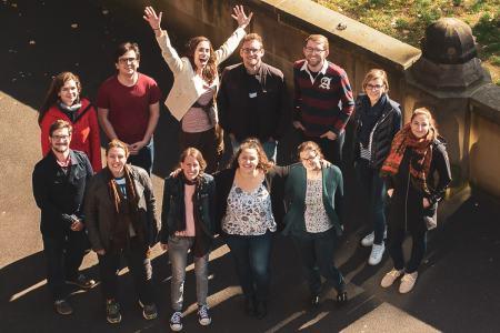 Ein Gruppenportrait aus der Vogelperspektive. Zu sehen sind zwölf Personen im Alter von ca. 20-35 Jahren. Die Chorleiterin hat begeistert die Arme nach oben gestreckt, die anderen haben auch gute Laune.